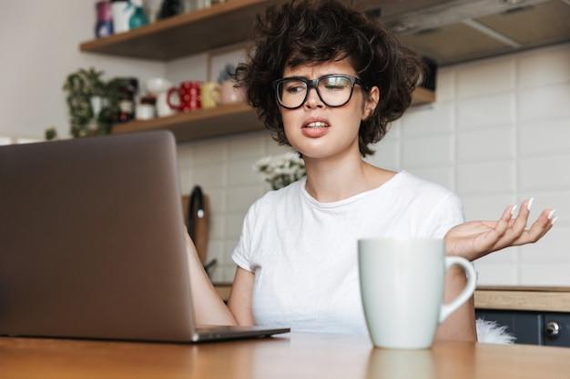 Ritratto di una giovane donna frustrata che indossa occhiali da vista lavorando sul computer portatile a casa la mattina