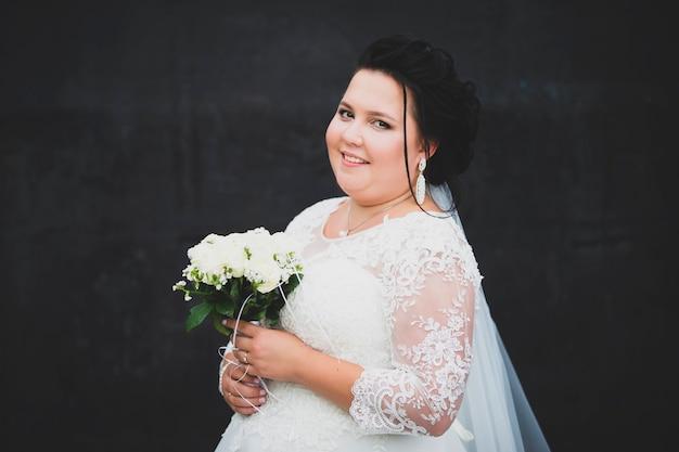 Ritratto di una sposa completa con un bouquet su uno sfondo scuro.