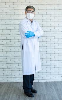 Il ritratto del medico o del ricercatore asiatico anziano integrale indossa il camice da laboratorio, gli occhiali trasparenti e la maschera per il viso in piedi e il braccio incrociato con sfondo di mattoni bianchi.