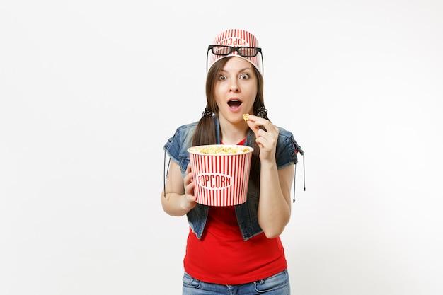 Ritratto di divertimento giovane donna attraente scioccata in occhiali 3d con secchio per popcorn sulla testa guardando film, mangiando popcorn dal secchio isolato su sfondo bianco. emozioni nel concetto di cinema.