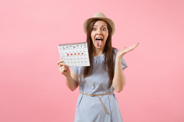Ritratto divertente giovane donna in abito blu, cappello che tiene il calendario dei periodi per controllare i giorni delle mestruazioni isolati su sfondo rosa di tendenza brillante. concetto medico, sanitario, ginecologico. copia spazio.