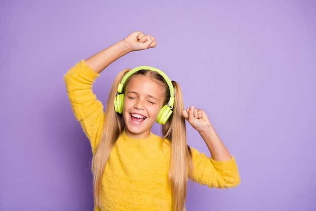 Ritratto di funky ragazzino pazzo con coda di cavallo ascolta musica fare pausa pausa usa auricolare cantare canzone danza su festa indossare ponticello alla moda isolato su parete di colore viola