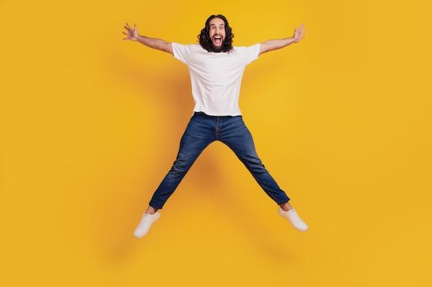 Il ritratto di un ragazzo positivo e sportivo funky fa un salto a forma di stella su sfondo giallo