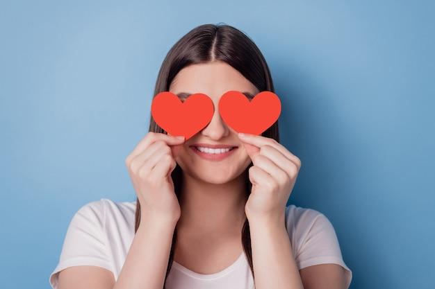 Ritratto di una simpatica e adorabile signora che tiene gli occhi chiusi sulla copertina della cartolina a forma di cuore rosso su sfondo blu