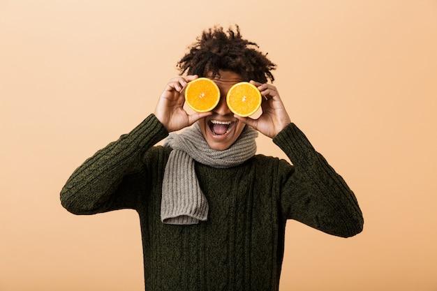 Ritratto di ragazzo afroamericano divertente che indossa un maglione e sciarpa che copre gli occhi con due pezzi di arancia, isolato sopra la parete beige