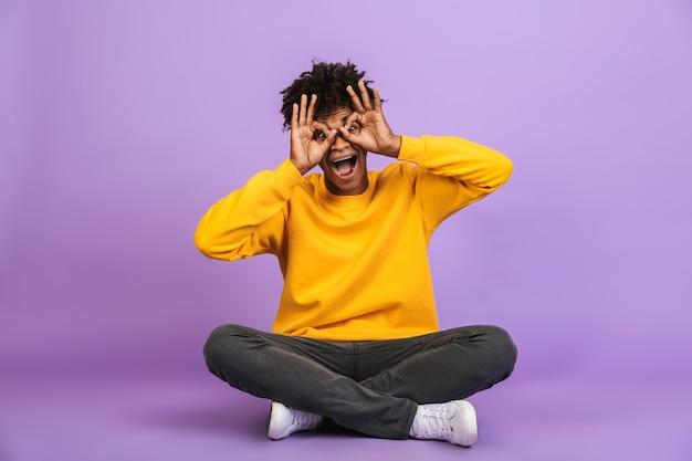 Ritratto di uomo afroamericano divertente seduto sul pavimento con le gambe incrociate e ti guarda attraverso il binocolo facendo con le dita, isolato su sfondo viola