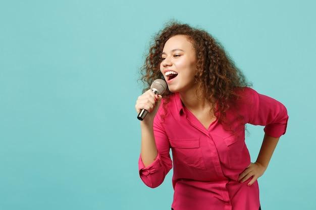 Il ritratto della ragazza africana divertente in vestiti casuali che balla, canta la canzone in microfono isolato sul fondo blu della parete del turchese in studio. persone sincere emozioni, concetto di stile di vita. mock up copia spazio.