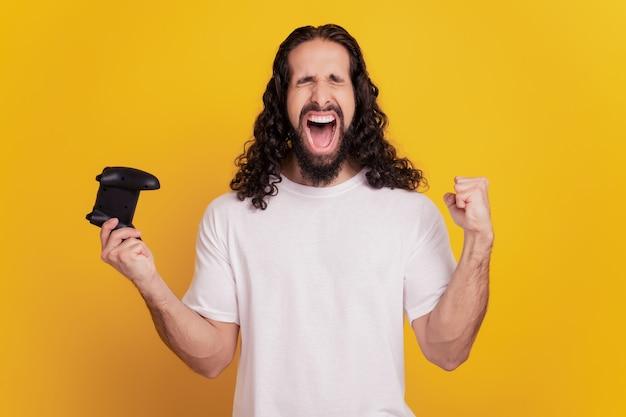 Ritratto di un giocatore divertente e stupito che tiene il joystick per giocare a un videogioco urlando su sfondo giallo
