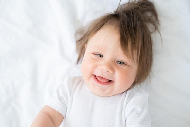 Ritratto di bambino divertente 6 mesi sorridente e sdraiato su una biancheria da letto bianca a casa.