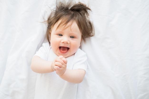Ritratto della neonata divertente 6 mesi che sorride e che si trova su una biancheria da letto bianca a casa.