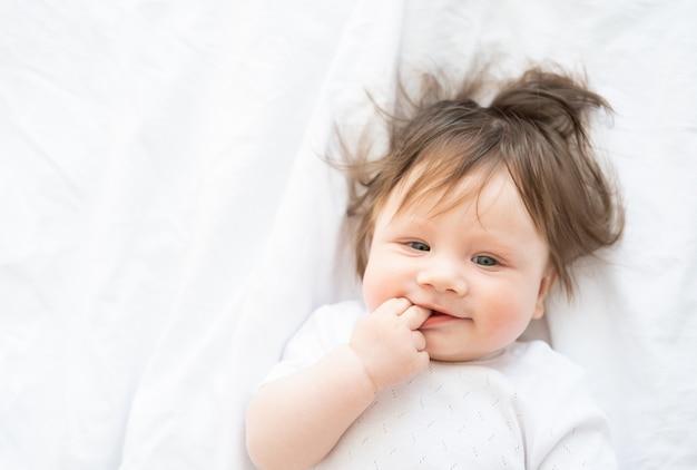 Ritratto di una bambina divertente con un dito in bocca che sorride e si trova su un letto bianco a casa