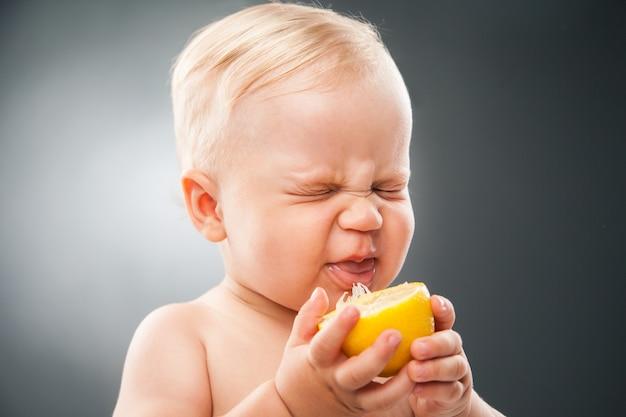 Ritratto di un bambino divertente che strizza gli occhi dal limone acido