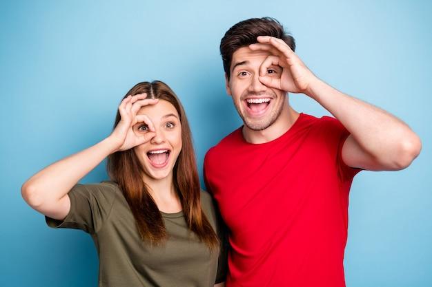 Ritratto di divertenti allegri funky due persone sposate mostrano segno ok fare binocolo guardare i vicini stupiti eccitati indossare abbigliamento stile casual isolato su sfondo di colore blu