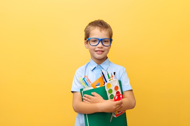 Ritratto di un ragazzo sorridente allegro divertente in una camicia blu con libri e cancelleria nelle sue mani