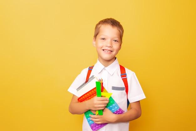 Ritratto del ragazzo caucasico sorridente allegro divertente in camicia bianca con lo zaino, tenente la cancelleria e pop it, su fondo giallo. il concetto di istruzione scolastica, cartoleria. di nuovo a scuola