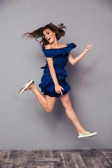 Ritratto di una donna allegra divertente che salta sul muro grigio