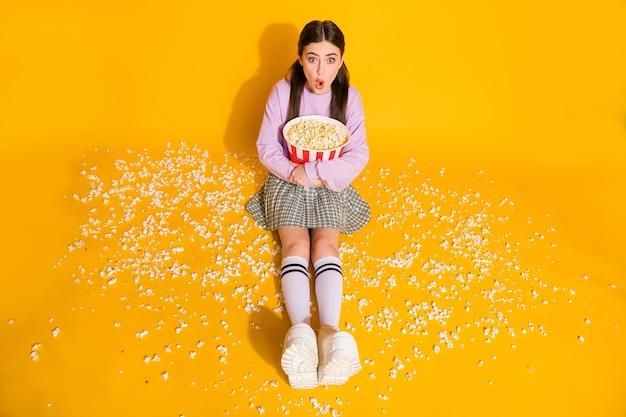 Ritratto di una ragazza goffa e divertente che tiene in mano un film di popcorn per guardare il film
