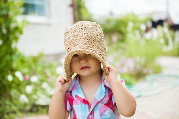 Ritratto di bambino carino divertente in cappello di paglia