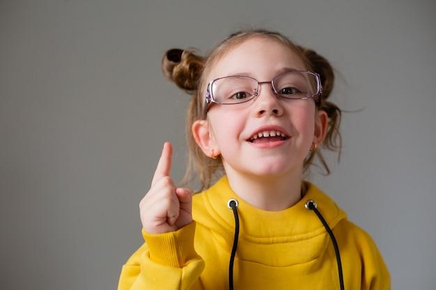 Ritratto di una bambina carina e divertente con occhiali con montatura nera in felpa con cappuccio gialla con un'acconciatura divertente