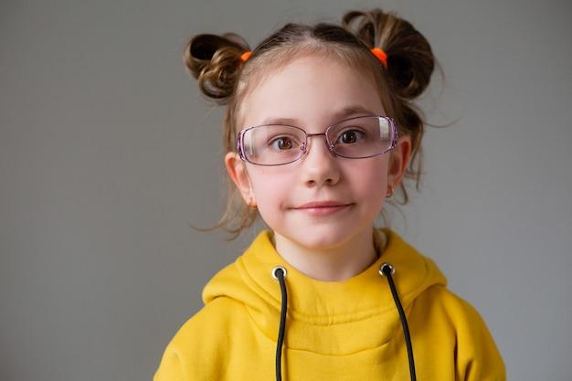 Ritratto divertente bambina carina su sfondo grigio che studia molto bambino stanco delle attività scolastiche