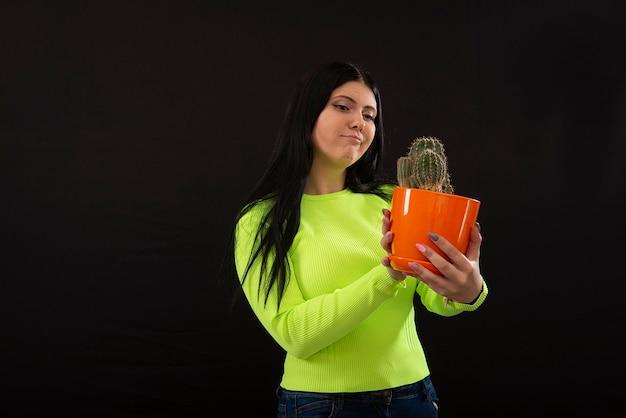 Ritratto della giovane donna del fronte divertente che tiene pianta in vaso del cactus isolata
