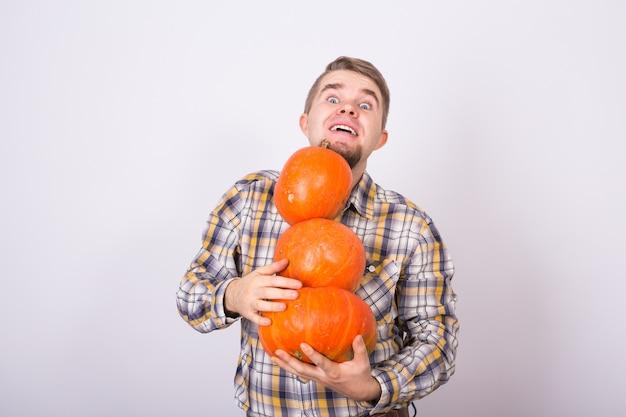 Ritratto di un contadino divertente in possesso di un zucche su uno sfondo chiaro studio