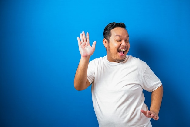Ritratto di un uomo asiatico grasso e divertente in maglietta bianca che sorride e balla felicemente