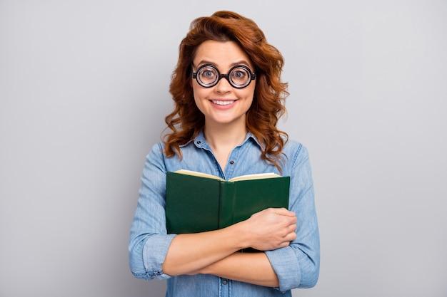 Il ritratto della donna allegra funky divertente in occhiali abbraccia il vestito alla moda di usura della storia del libro preferito isolato sopra il muro di colore grigio