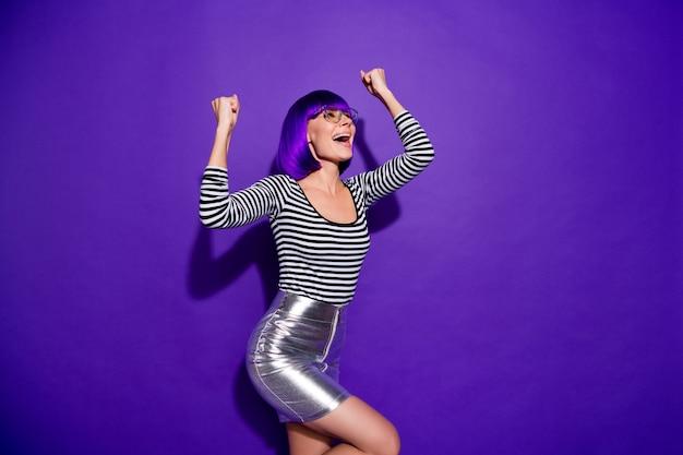 Ritratto di signora funky divertente che alza i pugni che gridano sì occhiali da vista vestiti isolati sopra fondo viola porpora