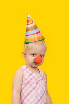 Ritratto di ragazza divertente con cappello da festa e naso rosso da clown su spazio giallo. cornice verticale.