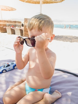 Ritratto di un ragazzino divertente che gioca e prova gli occhiali da sole sulla spiaggia del mare