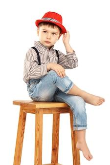 Ritratto di un ragazzino divertente seduto su uno sgabello alto in un cappello rosso isolato su bianco