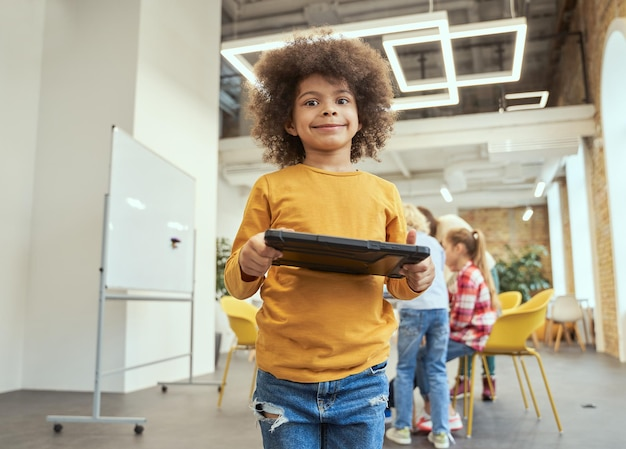 Ritratto di un ragazzino divertente che sorride alla telecamera tenendo in mano un tablet pc in piedi in un'aula durante