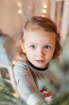 Ritratto di una bambina divertente con bellissimi occhi azzurri in pigiama alla moda che decora un albero di natale a casa. vacanze invernali e miracolo