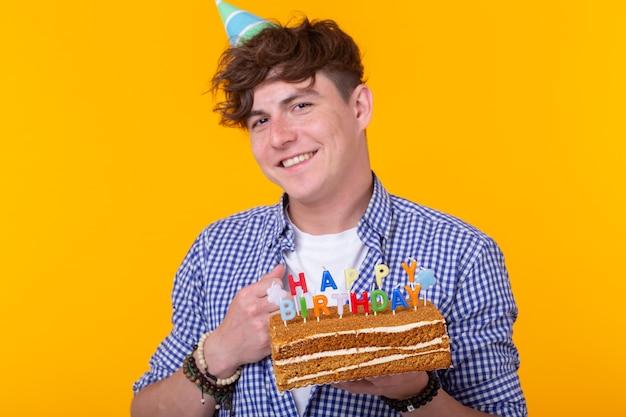 Ritratto di un ragazzo positivo divertente con un tappo di carta e bicchieri che tengono una torta di congratulazioni nelle sue mani su uno spazio giallo. concetto, divertimento e celebrazione. spazio pubblicitario.