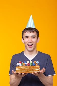 Ritratto di un ragazzo positivo divertente con un tappo di carta e bicchieri che tengono una torta di congratulazioni nelle sue mani su una superficie gialla. concetto, divertimento e celebrazione. spazio pubblicitario Foto Premium