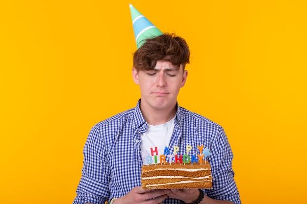 Ritratto di un ragazzo divertente e positivo con un tappo di carta e occhiali che tengono una torta di congratulazioni nelle sue mani su una superficie gialla