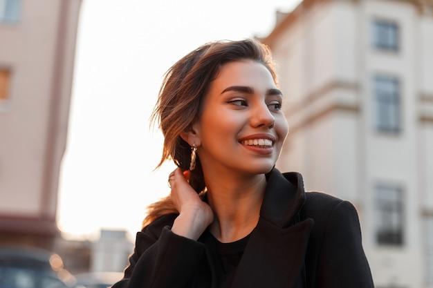 Ritratto di una bella giovane donna abbastanza felice divertente con un sorriso carino in un cappotto nero alla moda all'aperto in città in una luminosa giornata di sole