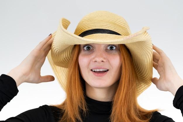 Ritratto di donna rossa divertente in cappello di paglia giallo borsa.