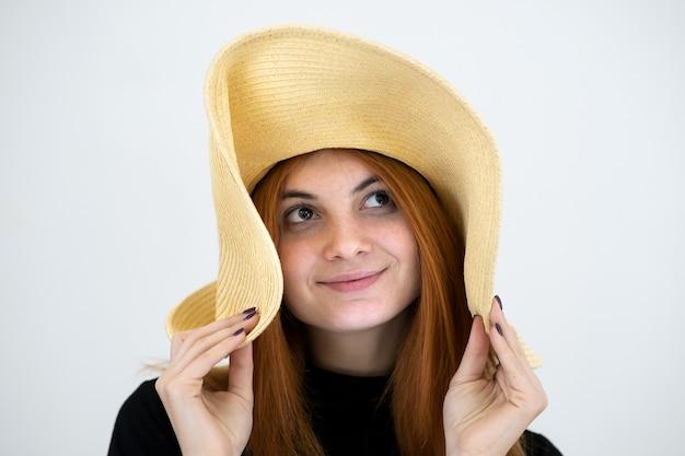 Ritratto di donna rossa divertente in cappello di paglia giallo
