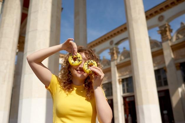 Ritratto di una donna sorridente divertente che tiene le ciambelle sul viso sullo sfondo della città in una giornata di sole
