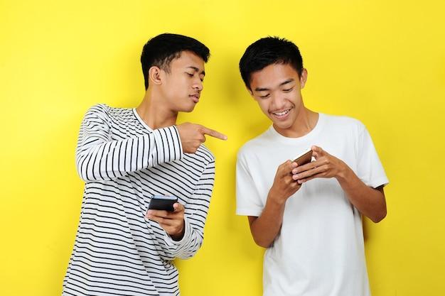 Ritratto di due simpatici giovani uomini asiatici che si guardano l'un l'altro i cellulari, isolati su sfondo giallo