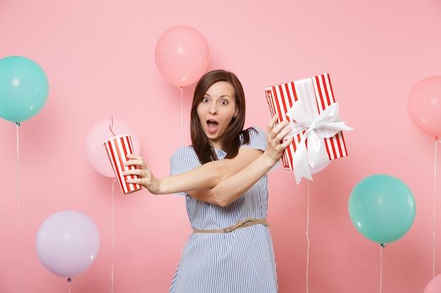 Ritratto di donna divertente in abito blu che tiene scatola rossa con regalo regalo e tazza di plastica di soda o cola su sfondo rosa con mongolfiere colorate. festa di compleanno, persone sincere emozioni.