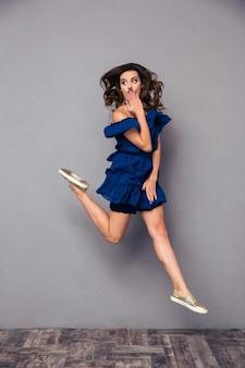 Ritratto di una donna divertente che salta e si copre la bocca sul muro grigio