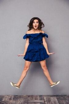 Ritratto di una donna divertente che salta sul muro grigio