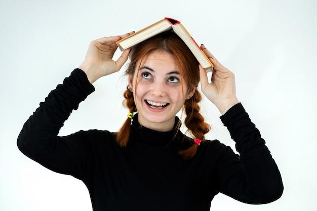 Ritratto di giovane ragazza sorridente divertente dello studente con un libro aperto sulla sua testa. concetto di lettura ed educazione.