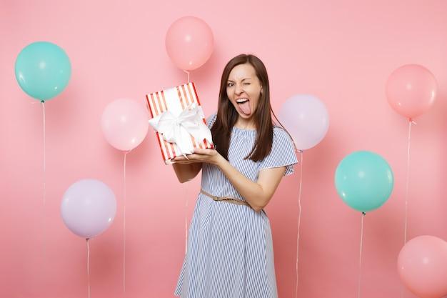 Ritratto di una giovane donna divertente in abito blu che lampeggia mostrando la lingua che tiene la scatola rossa con un regalo presente su sfondo rosa con mongolfiere colorate. festa di compleanno, persone sincere emozioni.
