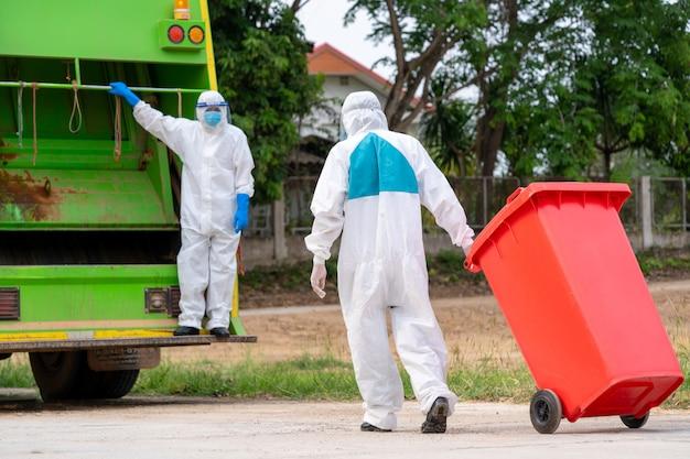 Ritratto di un bidone della spazzatura in indumenti protettivi dpi dpi indossano gomma medica con camion carico rifiuti e cestino, coronavirus disease 2019, coronavirus si è trasformato in un'emergenza globale.