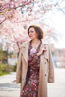Ritratto di una donna gentile sullo sfondo di fiori di sakura. passeggia nel giardino fiorito di sakura. giovane donna alla moda che sta nel parco di sakura e che gode della bellezza
