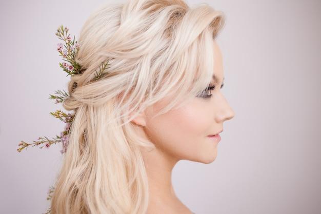 Ritratto di giovane donna delicata con capelli biondi. acconciatura alla moda